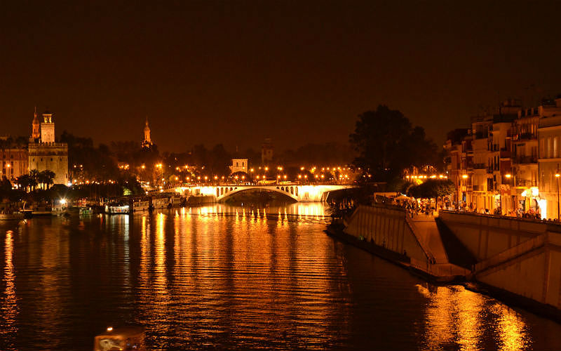 the Guadalquivir River at night with the Torre del Oro in the background