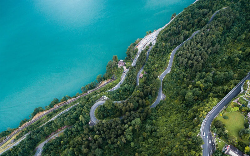 A winding road up a mountain taken from a drone
