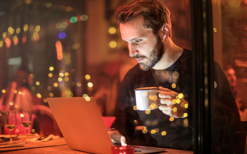 Man drinking coffee while woking is not how to protect your laptop from physical damage
