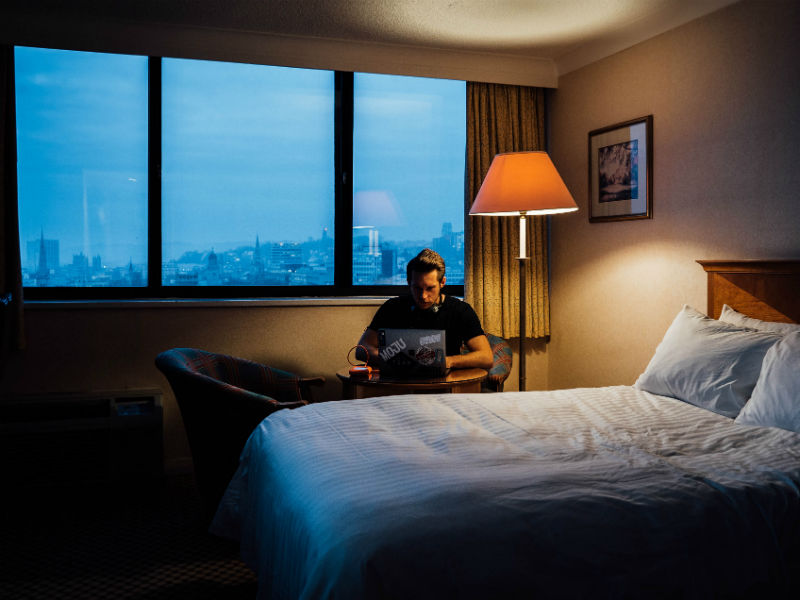 A man sat in a hotel room using a laptop