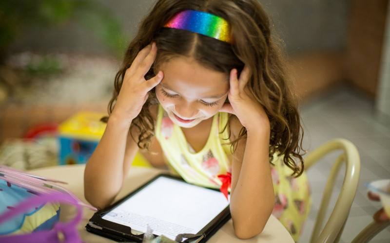 A young girl reading from a tablet