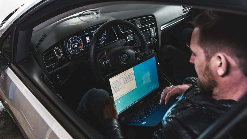 Man looking at how to use a laptop in a car