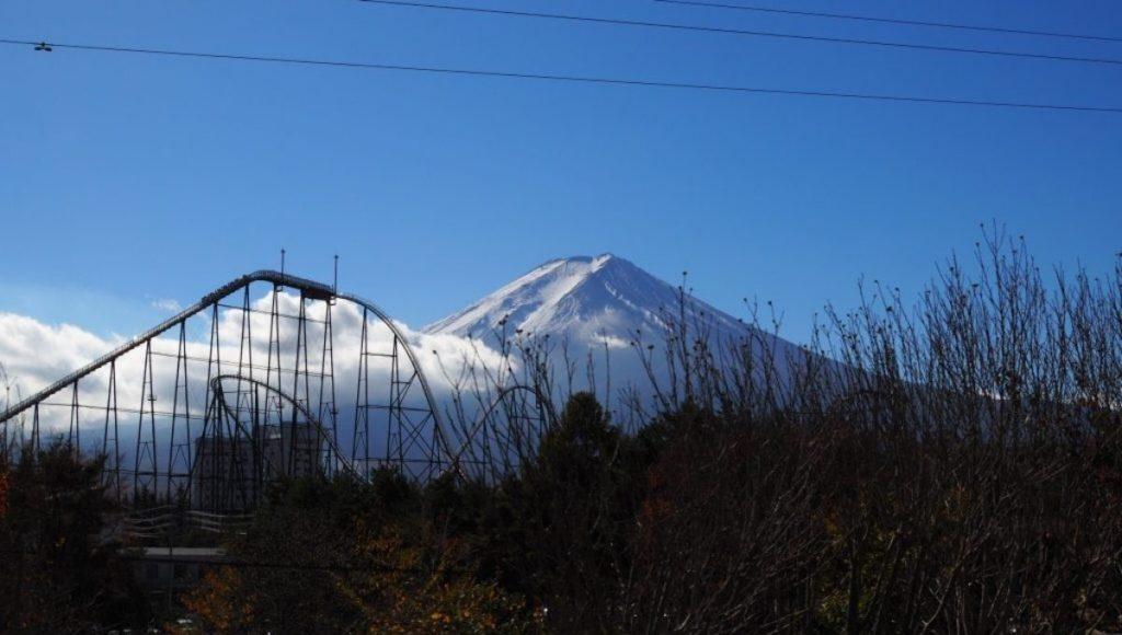 Riding a roller coaster while admiring a great view of Mount Fuji