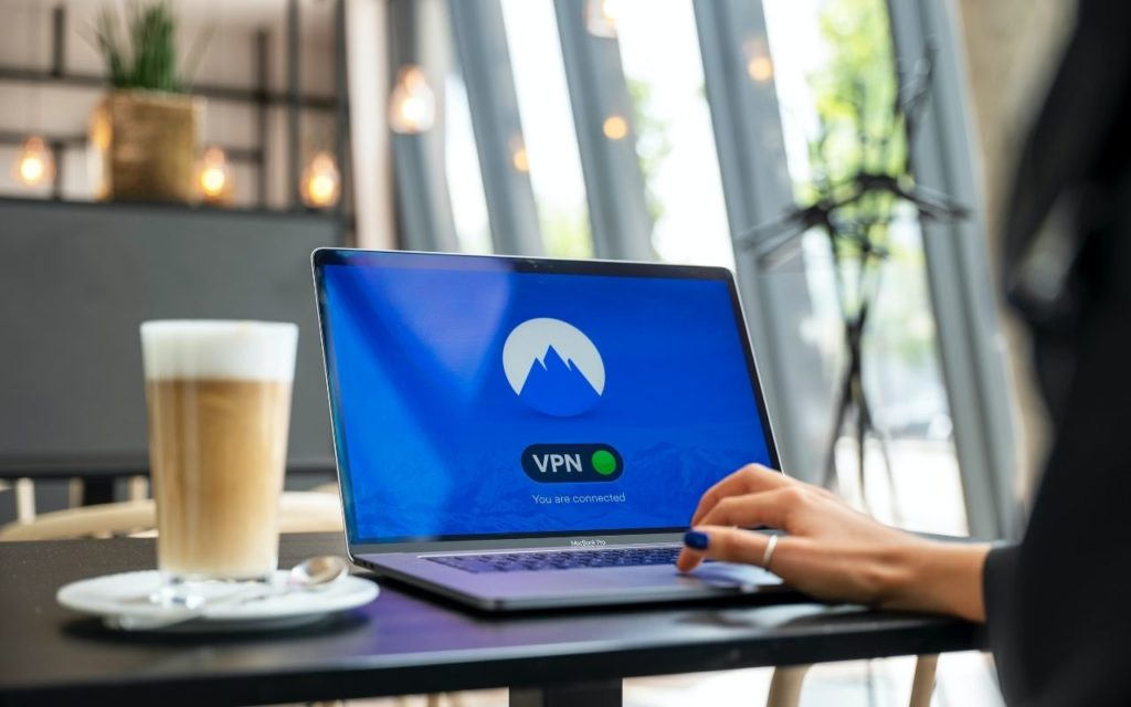 A lady using the Best VPN For Travel while connecting to the internet in a local coffee shop over public wi fi