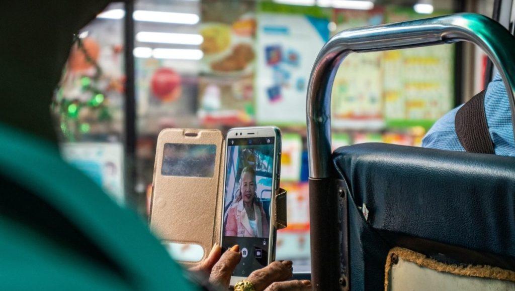 A lady using a phone with a Thai SIM card