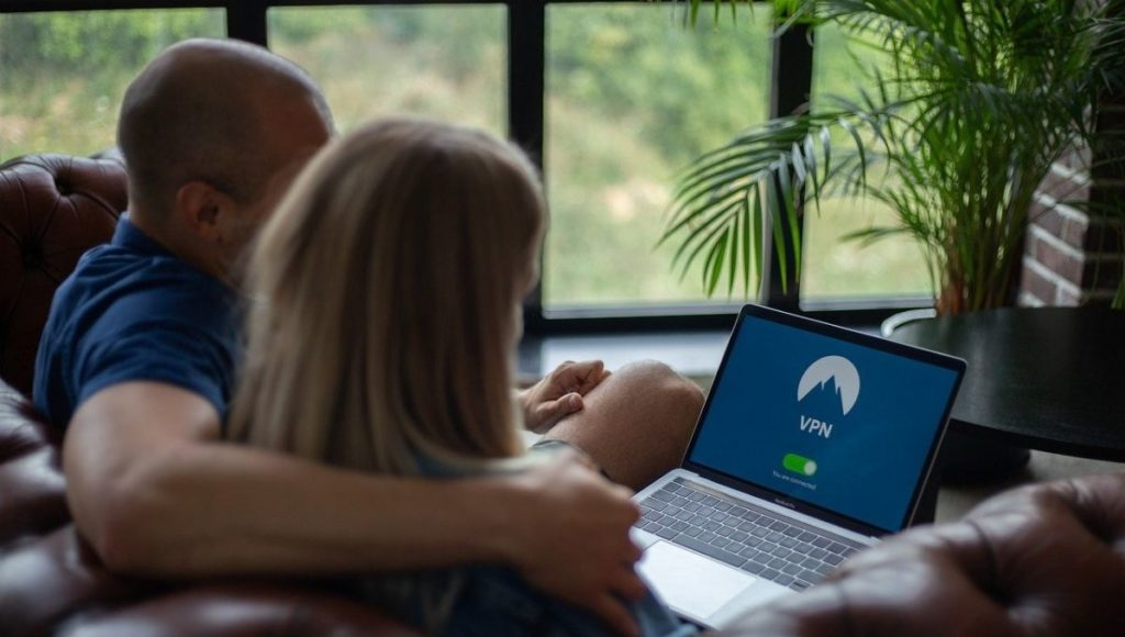 two people on a laptop using a VPN: Free vs Paid VPN