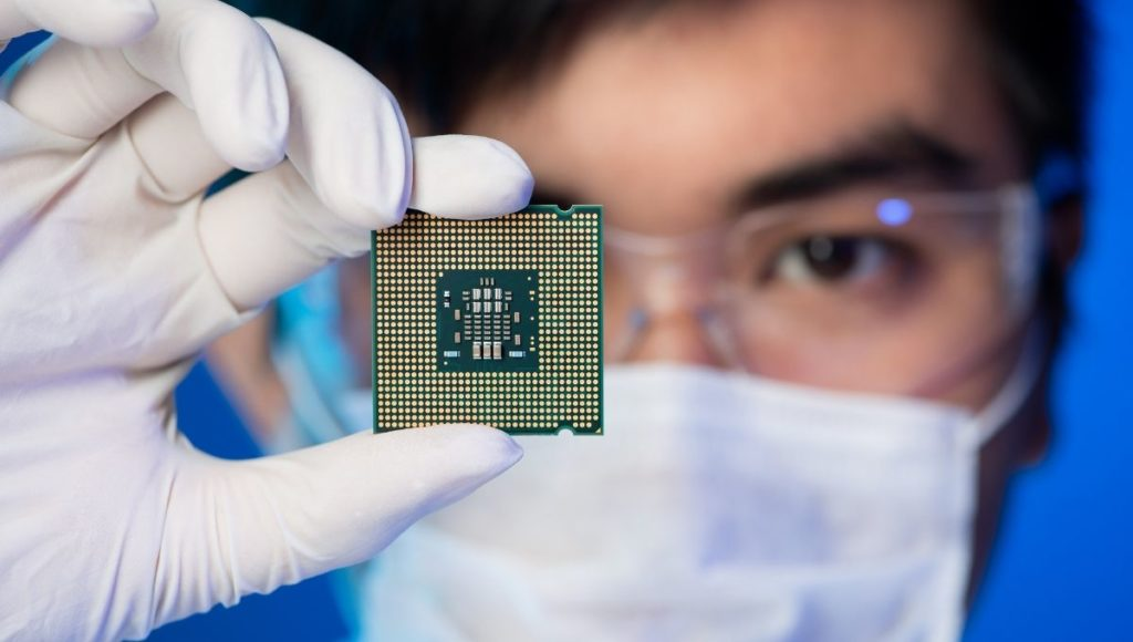 A scientist holding up a processor