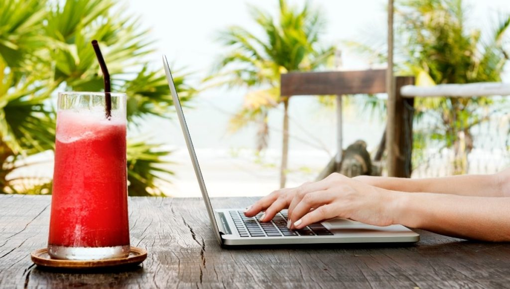 A travel blogger using a laptop by the beach