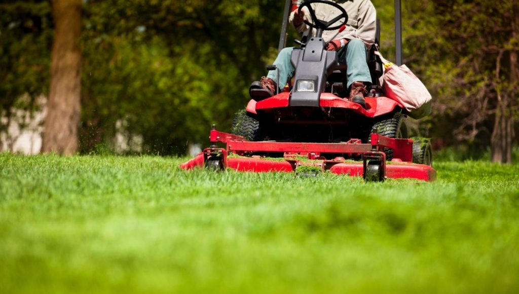 A person mowing the lawn with a ride on lawn mower