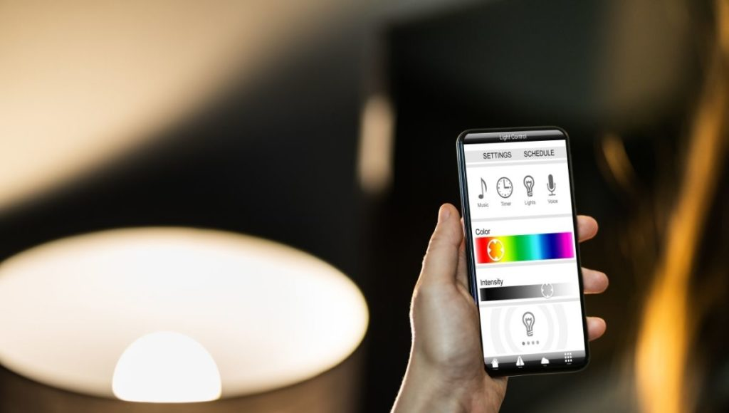 A man using a smart lighting system with his smart phone