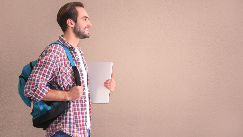 male college student with backpack and laptop