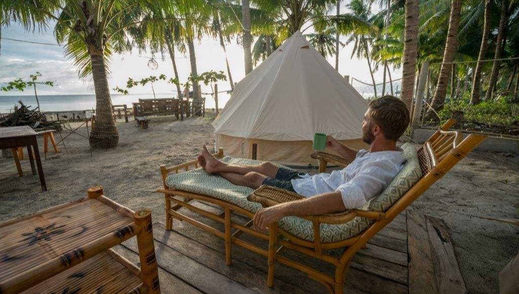 Travel man relaxing in glamping site in the philippines