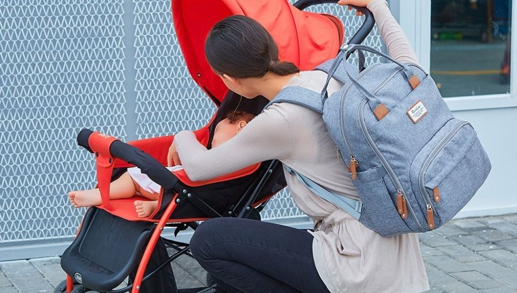 A mother carries a diaper bag in her backpack and the baby sleeps in the stroller