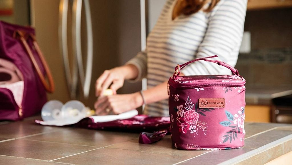A woman packing her cooler bag for traveling with frozen breast milk