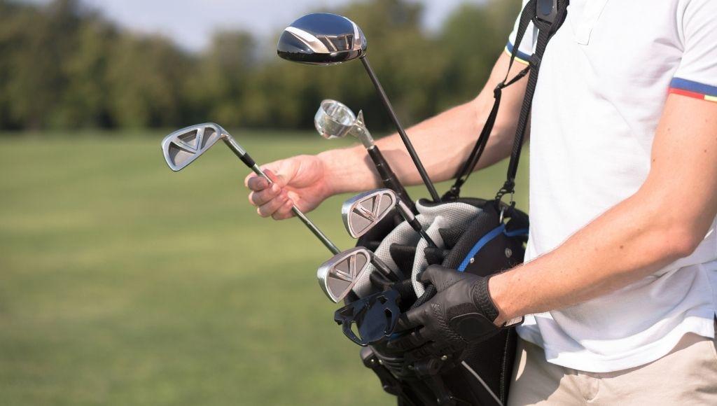 A man carries her golf clubs bag