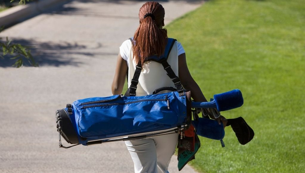 A yang girl carry golf clubs in her backpack