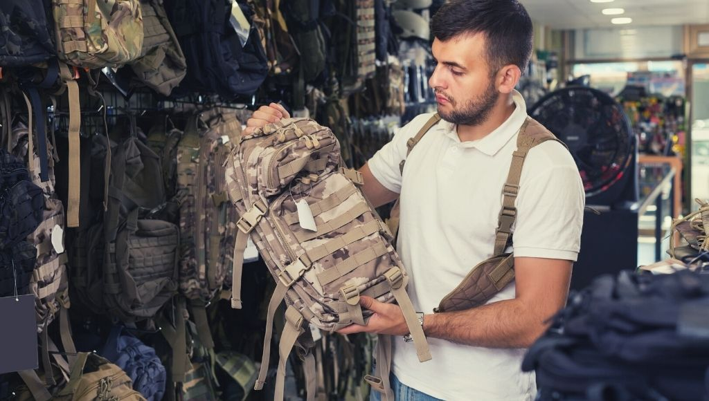 A military boy has arrived at a tactical backpack shop for buying a military backpack