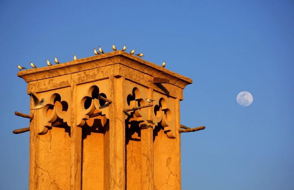 The moon behind a temple in the Al Bastakiya Quarter of Dubai